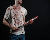Bloody topic: The guy in a bloody T-shirt holding a bloody bat on a black background — Stock Photo