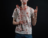 Bloody topic: The guy in a bloody T-shirt holding a bloody bat on a black background — Stok fotoğraf