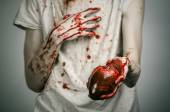 Bloody Halloween theme: crazy killer keeps bloody hands torn bloody human heart and experiencing depression and pain — Stock Photo