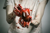 Bloody Halloween theme: crazy killer keeps bloody hands torn bloody human heart and experiencing depression and pain — Stockfoto