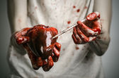 Social advertising and the fight against drug addiction: bloody hands addict holding syringe and bloody human heart — Stock Photo