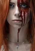 Girl with red hair, bloody face, a chain with a cross, blue eyes, vampire, murderer, psycho, halloween theme, studio shot, bloody woman — Stockfoto