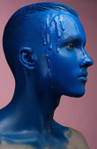 Portrait of a man poured blue paint on a pink background — Stock Photo