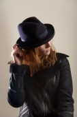 Redhead touching brim of blue felt hat — Stock Photo