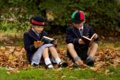 Brother and sister reading among autumn leaves — Stock Photo