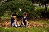 Brother and sister sitting on autumn leaves — Stok fotoğraf