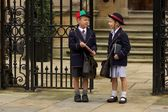 Brother and sister talking at school gates — Stok fotoğraf