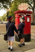 Schoolboy turning while posting letter with sister — Stock Photo