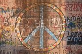 Peace symbol and graffiti spray-painted on wall — Stock Photo