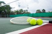 Close up view of tennis racket and balls on the tennis court — Stock Photo