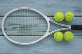 Close up view of tennis racket and balls on the wooden table — Stock Photo