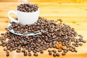 Coffee beans on cup and wooden table  — Stok fotoğraf