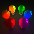 Colored glowing light bulbs standing on dark — Stock Photo #67249301