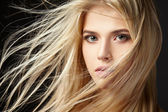 Portrait of blonde girl with fluttering hair — Stock Photo