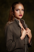 Beautiful girl in fashionable coat on dark background. — Stock Photo
