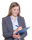 Laughing german businesswoman with clipboard — Stock Photo