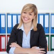 Laughing businesswoman with blonde hair and dark eyes at office — Stock Photo #77501438