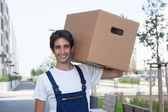 Laughing hispanic removal man with box — Stock Photo