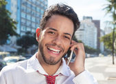 Successful latin businessman at phone in the city — Stock Photo