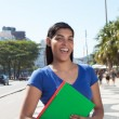 Laughing latin student with long dark hair in the city — Stockfoto #82772408