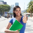 Latin student with long dark hair in the city showing thumb — Stockfoto #82772612