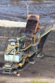 Heavy construction tipper trucks dump coal to the conveyor at co — Stock Photo