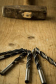 Drill bits on wooden table — Stock fotografie