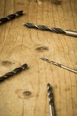 Drill bits on wooden table — ストック写真