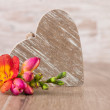 Wooden heart and colorful freesia flower — Stock Photo #61669653