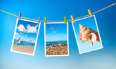 Sea pictures hanging on colorful pegs — Stock Photo