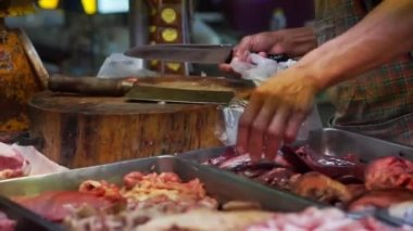 Butcher selling fresh meat in local Asian market, unhygienic food preparation — Stock Video