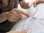 Male tourist pointing in map — Stock Photo