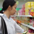 Bangkok, Thailand - April 2015  -Asian girl, woman walking, looking and shopping snacks in supermarket isle — Stock Video #69640793