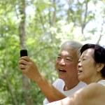 Asian senior couple using cell phone — Stock Photo #74487155