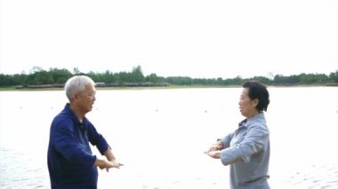 Video of Asian Senior Elderly couple Practice Taichi, Qi Gong exercise outdoor next to the lake — Stock Video