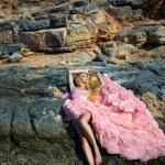 Beautiful blond woman sexy pink ballroom dress standing on the rocks in Santorini — Stock Photo #60980849