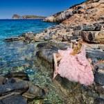 Beautiful blond woman sexy pink ballroom dress standing on the rocks in Santorini — Stock Photo #60980867