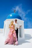 The lovely young couple beautiful woman from handsome man relating to the chapel with the blue roof in santorini — Stock Photo