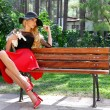 Beautiful blond woman in a black hat with long legs sitting on a bench holding the cute cat — Stock Photo #70475949
