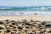 Wave of the sea on the sand beach with sea stones in the front — Stock Photo