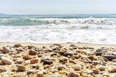 Onda del mar en la playa de arena con piedras de mar en la parte delantera — Foto de Stock