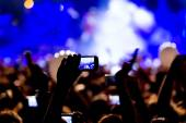 People taking photographs with touch smart phone during a music  — Stock Photo