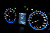 Backlit gauges of an automobile. Blue glowing meters with a whit — Stock Photo