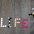 The word life written whith pills on a wooden background. — Stock Photo #70936945