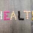 The word health written whith pills on a wooden background. — Stock Photo #70938037