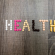 The word health written whith pills on a wooden background. — Stock Photo #70938891