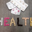 The word health written whith pills on a wooden background. — Stock Photo #70939193