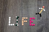 The word life written whith pills on a wooden background. — Fotografia Stock