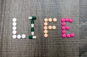 The word life written whith pills on a wooden background. — Foto Stock