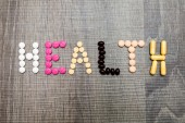 The word health written whith pills on a wooden background. — Foto Stock